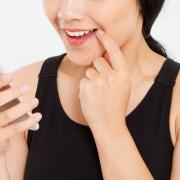 kobieta trzyma i odczytuje informacje ze smartfona